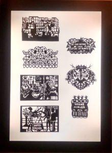 Eksempler på papirklip i sort, udstillet i lyspanel på Papirmuseet i Silkeborg